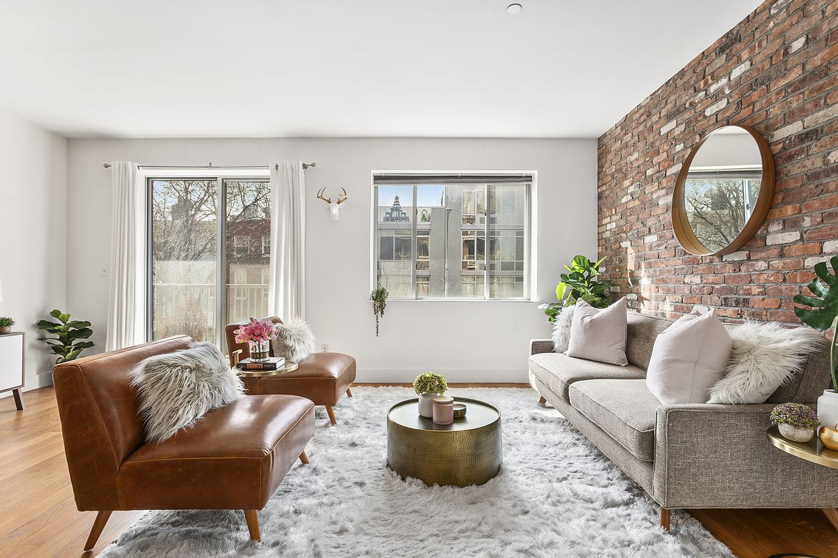 The living room has one exposed brick wall, one large window, and a sliding glass door that lets out onto a west-facing patio.