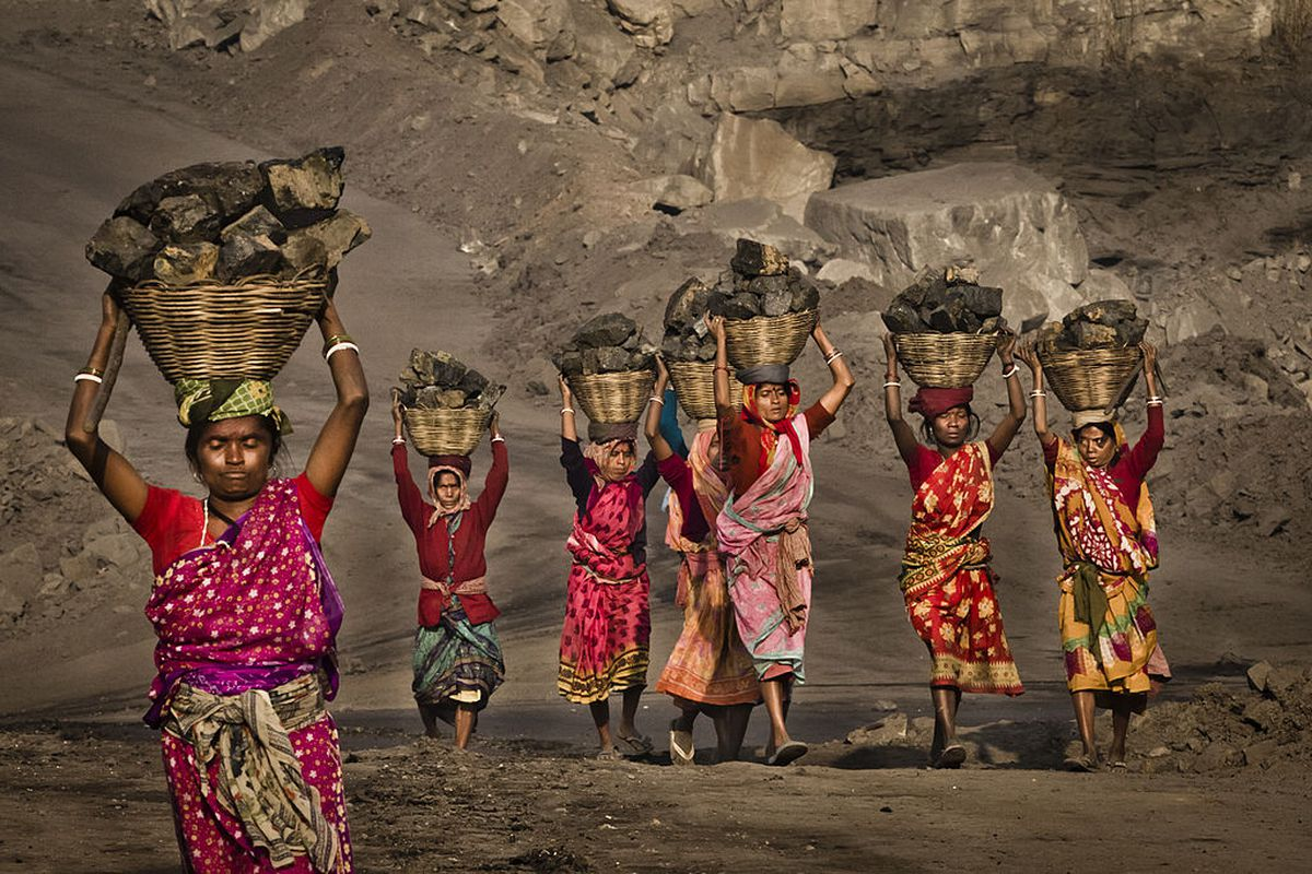 Indian villagers, illegally scavenging coal from a nearby mine.