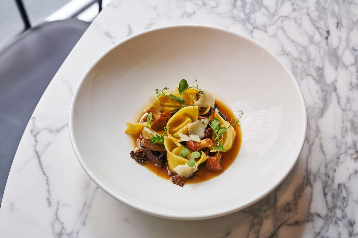 Cappellaccipasta with sheep's milk ricotta, wild mushrooms, and pine nuts in a white bowl