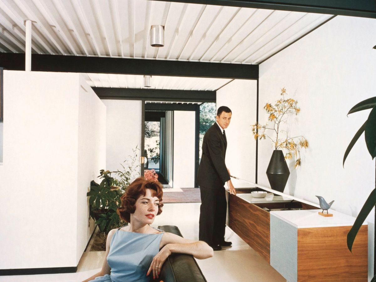 A woman sits on a black sofa in a sparsely furnished room. A man standing at a long bureau looks at her.