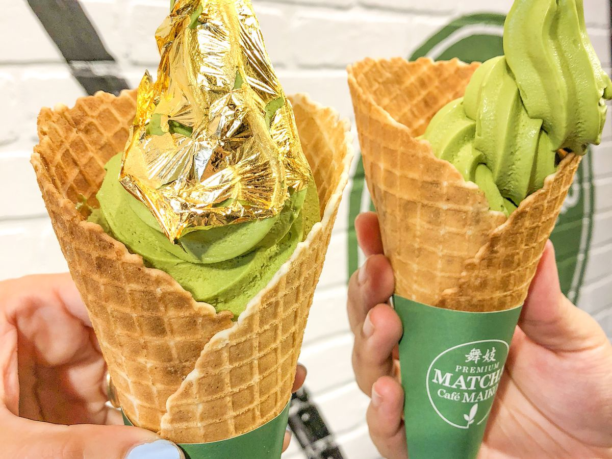 Two match soft-serve ice cream waffle cones, one covered with a gold paper layer