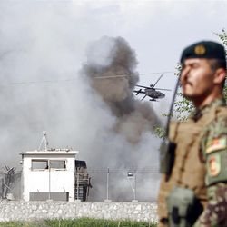 An Afghan soldier stands guard as a helicopter flies low over the scene of a suicide attack on the U.S.-led provincial reconstruction team (PRT) compound in the Behsood district of Jalalabad, east of Kabul Afghanistan, on Sunday, April 15, 15 2012. The Taliban launched a series of coordinated attacks on at least seven sites across the Afghan capital on Sunday, targeting NATO headquarters, the parliament and diplomatic residences. Militants also launched near-simultaneous assaults in three other eastern cities. (AP Phot/Rahmat Gul)