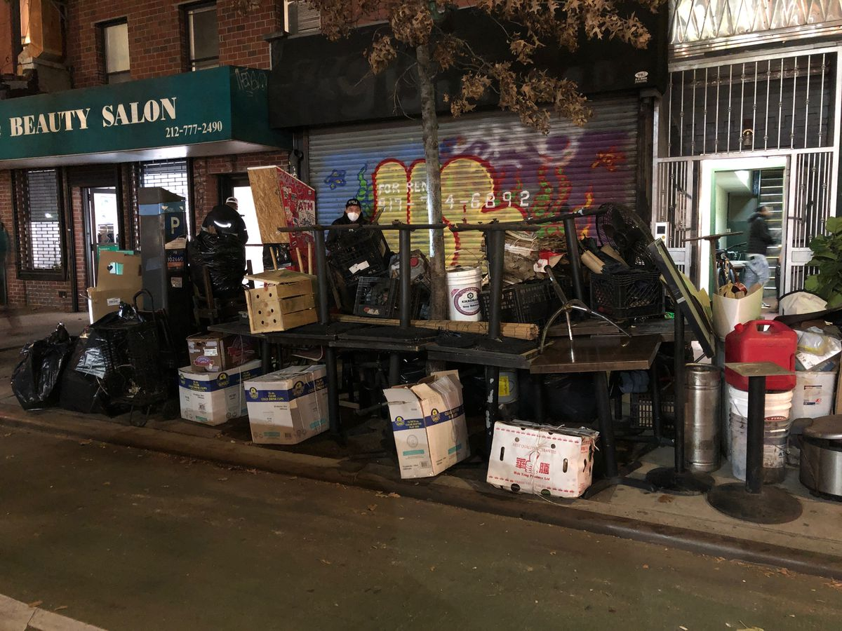 A dark photo of a bunch of tables and kitchen equipment and black plastic garbage bags piled on the sidewalk in front of a pulled down graffitied grate where Ugly Kitchen restaurant used to be located.