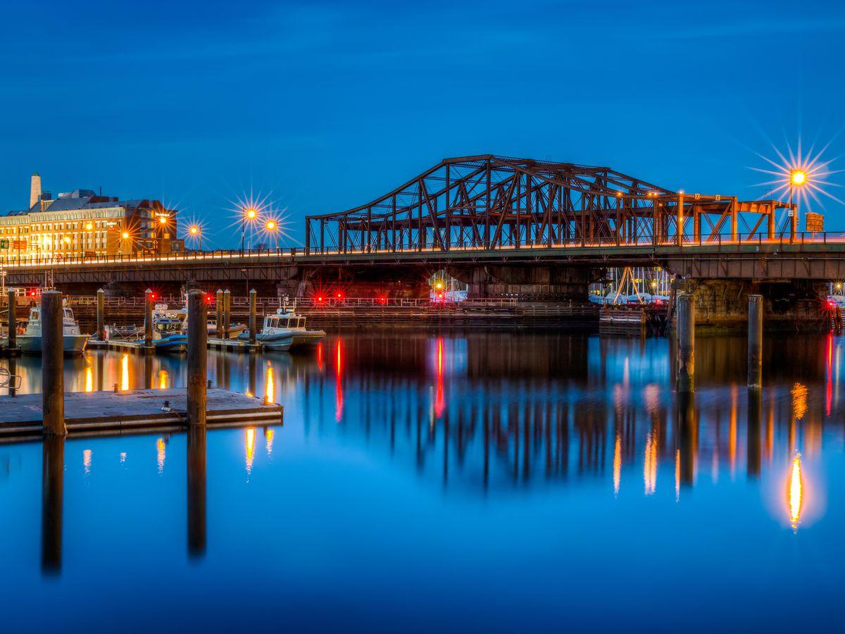An iron bridge over a river at nighttime.
