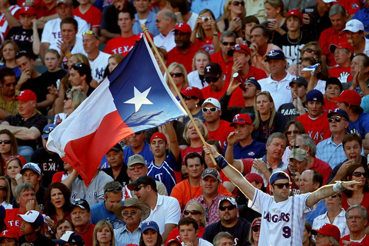 A fan holds up the Texas state flag during Game Two of the ALCS during the 2010 MLB Playoffs at Rangers Ballpark in Arlington on October 16 2010 in Arlington Texas.  (Photo by Stephen Dunn/Getty Images)