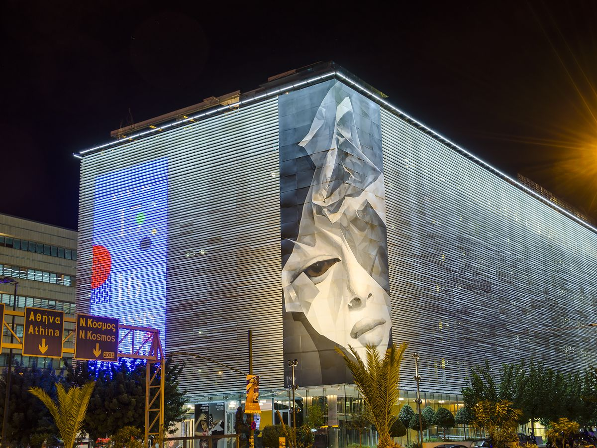 The exterior of the Onassis Cultural Center in Athens. The building facade consists of glass and traditional marble.