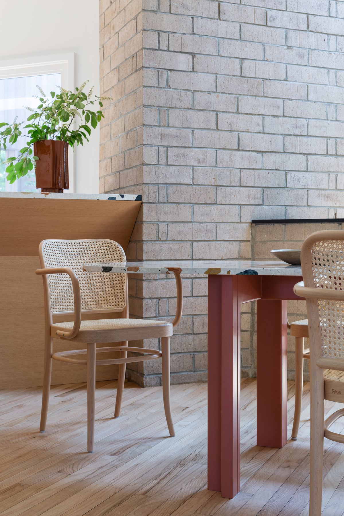 A dining area with pale wood chairs with woven back and rounded arm chairs. A table with terrazzo surface and rust red legs sits in front of a brick fireplace.