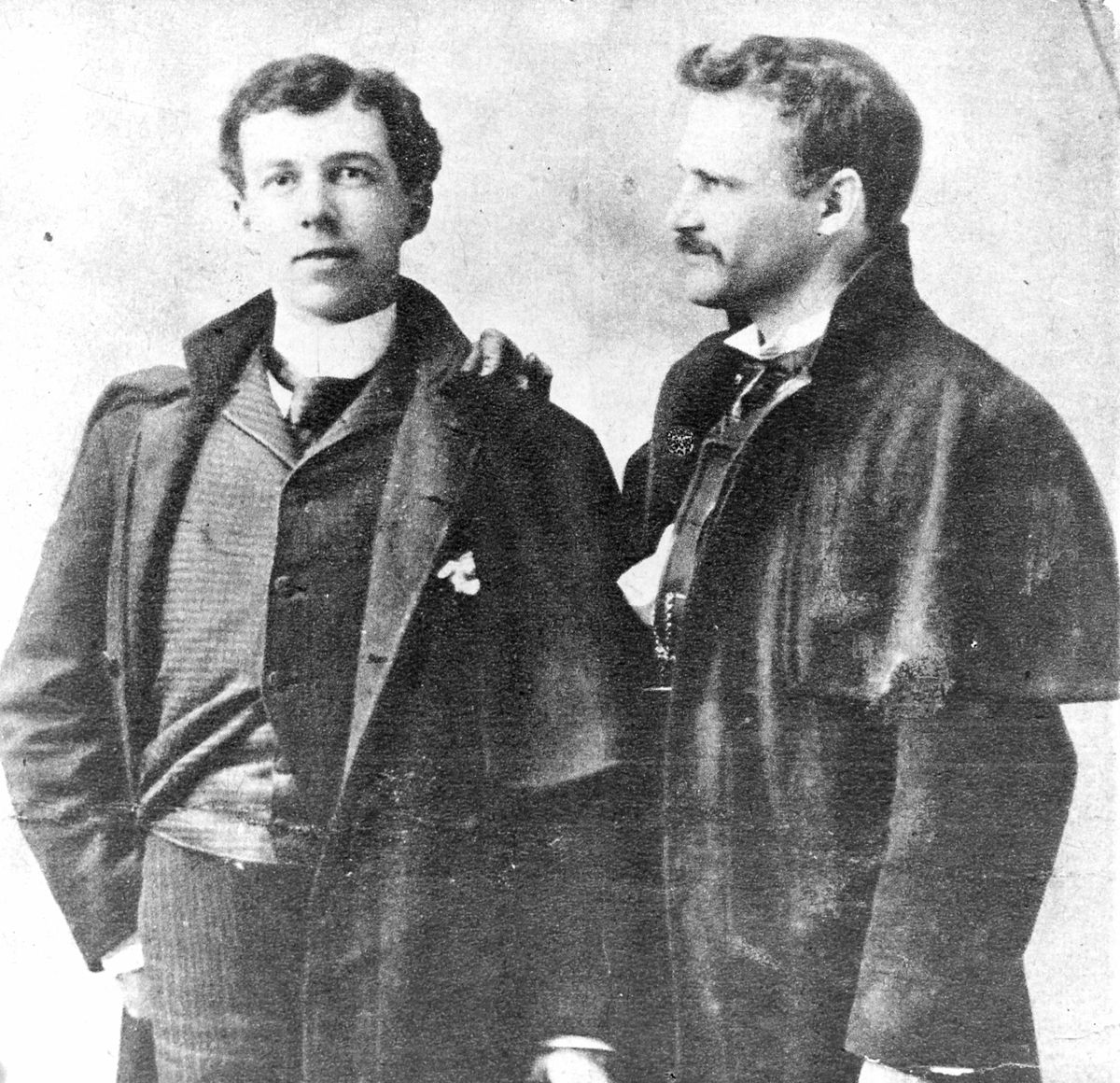 Two late-19th century architects in Chicago pose for a portrait.