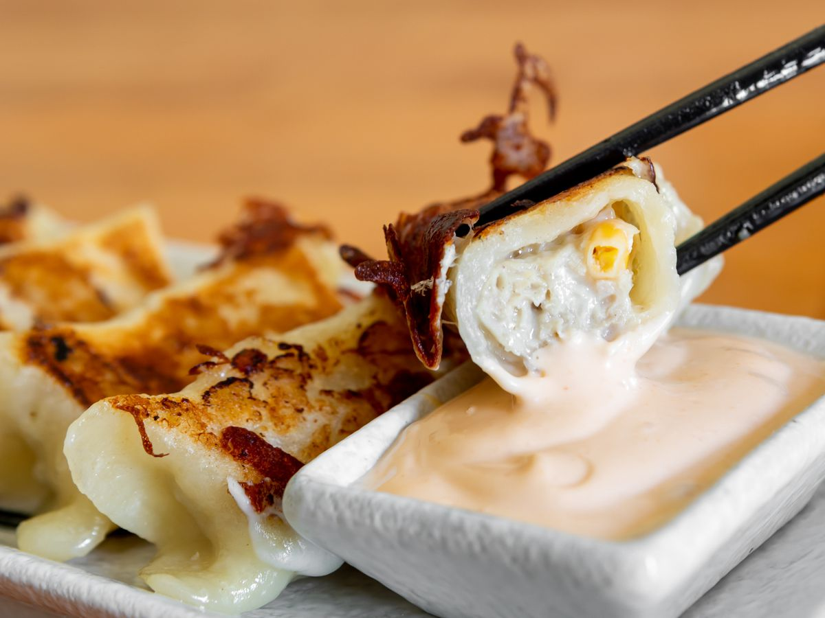 A potsticker, held by a pair of chopsticks, being dipped into a creamy sauce
