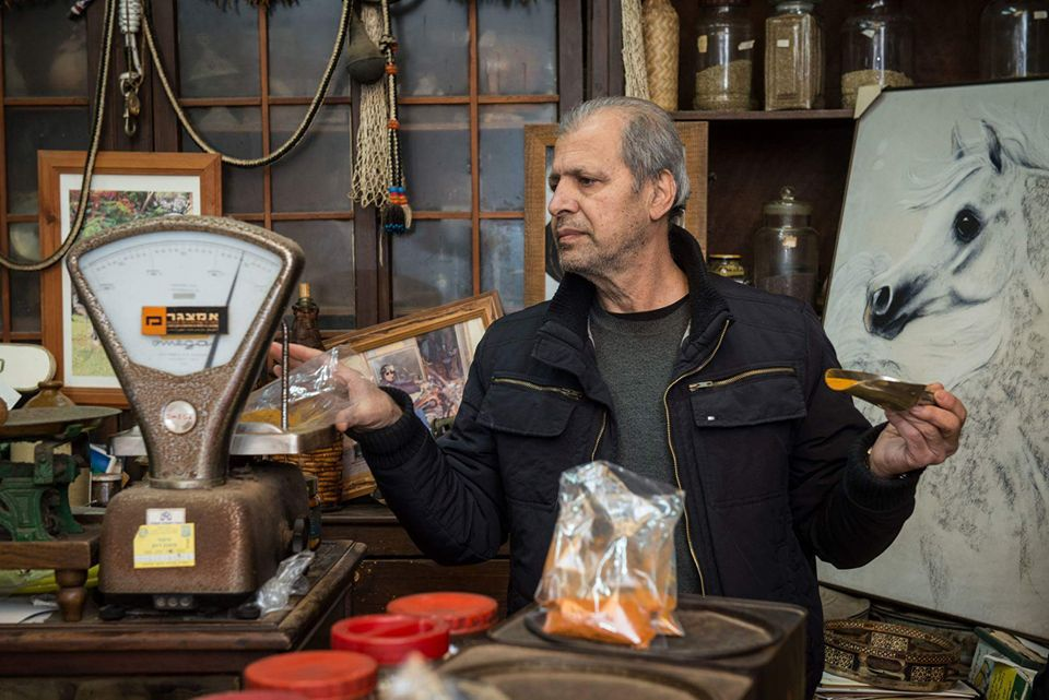 A man weighs a plastic bag of spices on an old-fashioned scale with a scooper in his other hand as he stands in a shop full of bric-a-brac