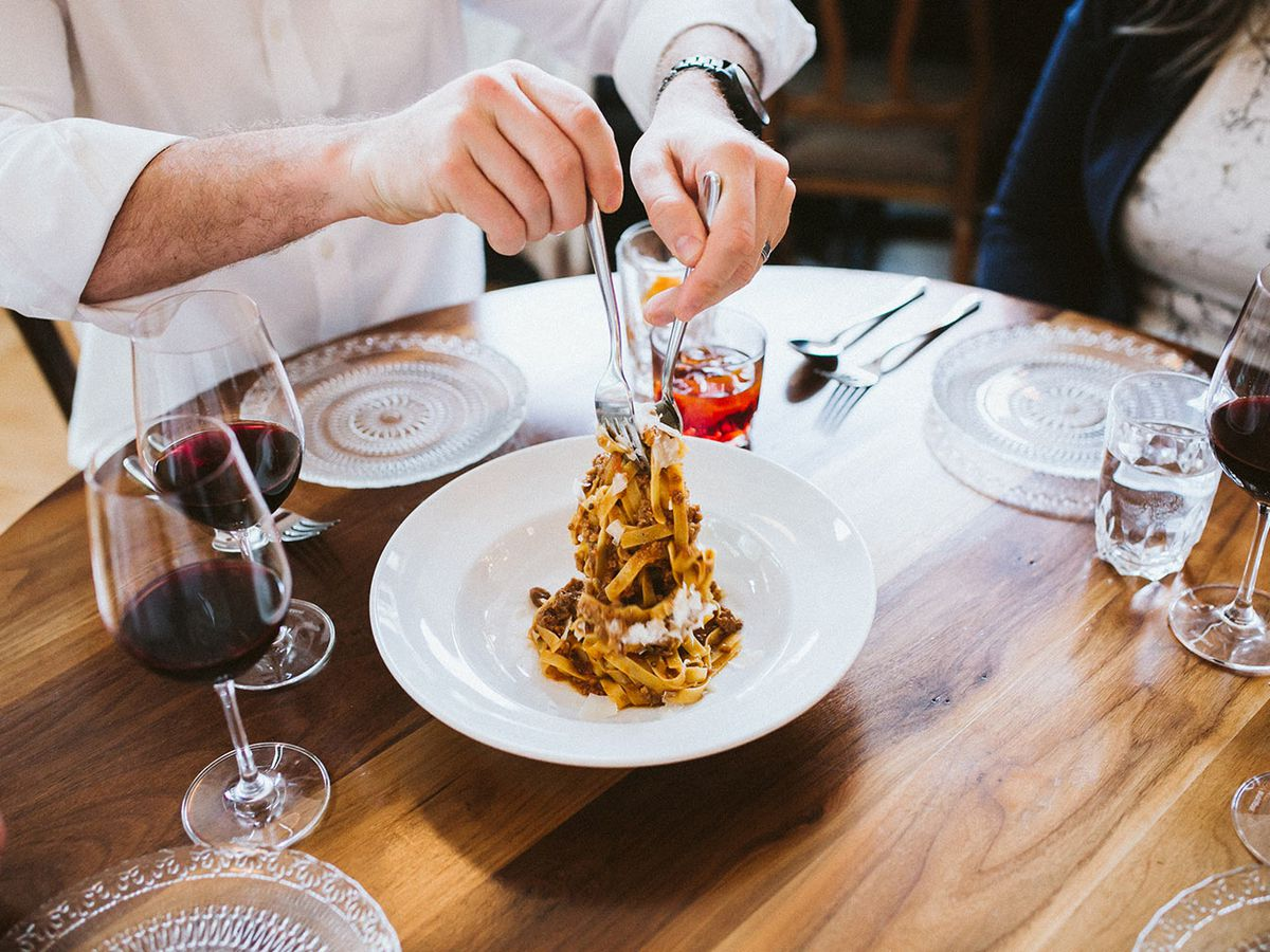 A server lifts a clump of pasta from a plate with two forks, with glasses of red wine and small empty plates set around on a wooden table
