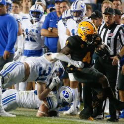 Arizona State running back Daniyel Ngata (4) gets tackled by BYU defenders during an NCAA college football game at LaVell Edwards Stadium in Provo on Saturday, Sept. 18, 2021.