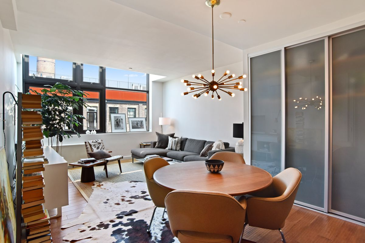 A living area with hardwood floors, a modern light fixture, a round dining table, and a skylight.