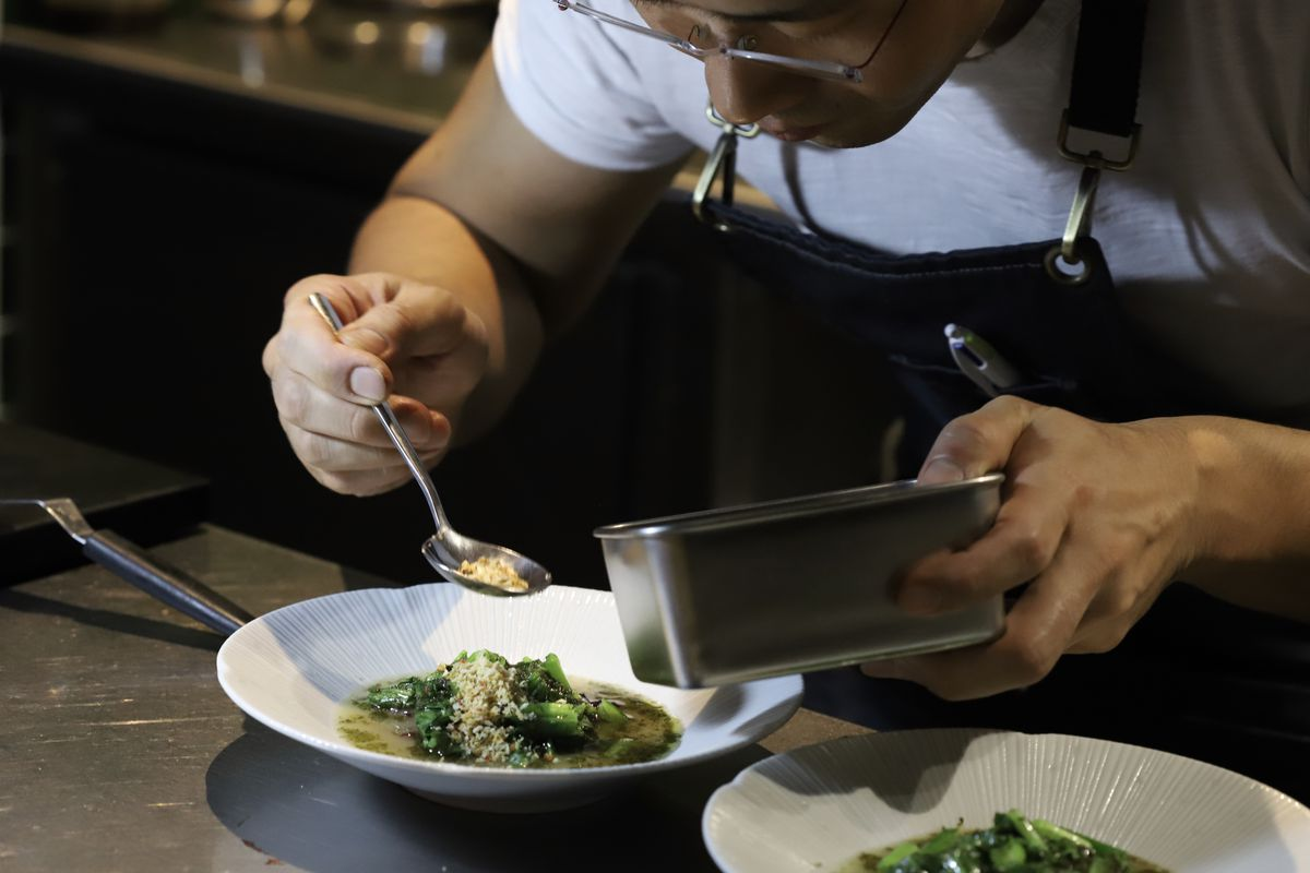 Zijun Meng plating a dish at TāTā Eatery's counter at Tayer and Elementary — one of London's best restaurants — on Old Street in Shoreditch, east London