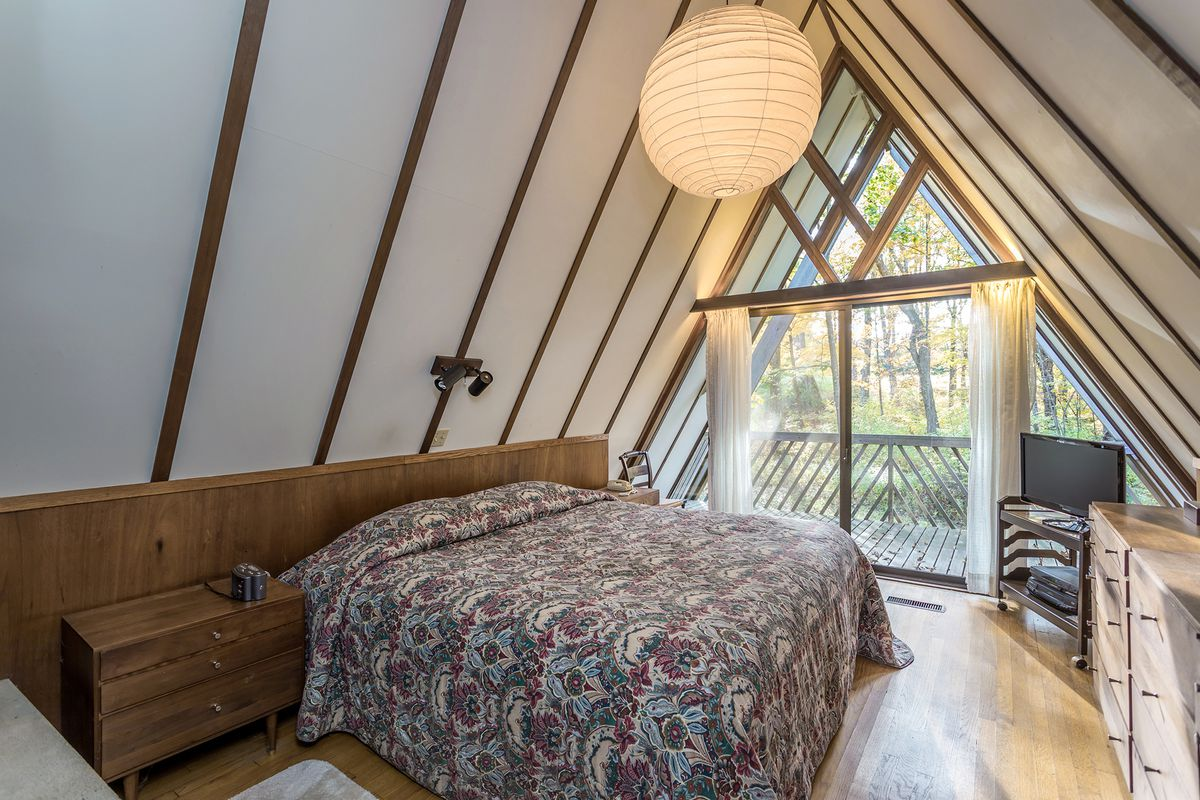 A bedroom with a large white light, flower bedspread, and wood furniture.