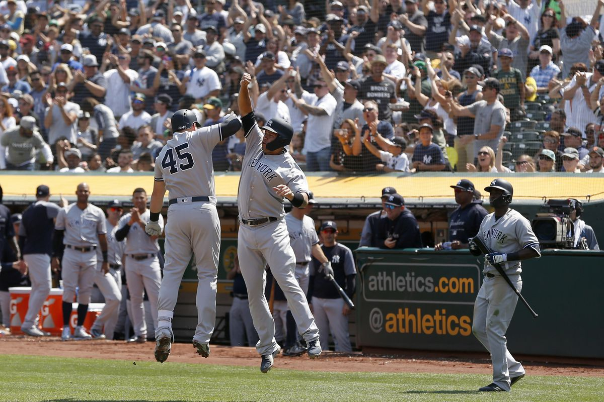 Luke Voit is congratulated by Gary Sanchez after hitting a two-run home run against the Athletics in the second inning at Oakland Coliseum.