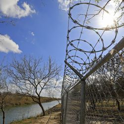 A view of the Rio Grande and the fence surrounding the migrant camp in Matamoros, Tamaulipas, Mexico, on Tuesday, Feb. 23, 2021.