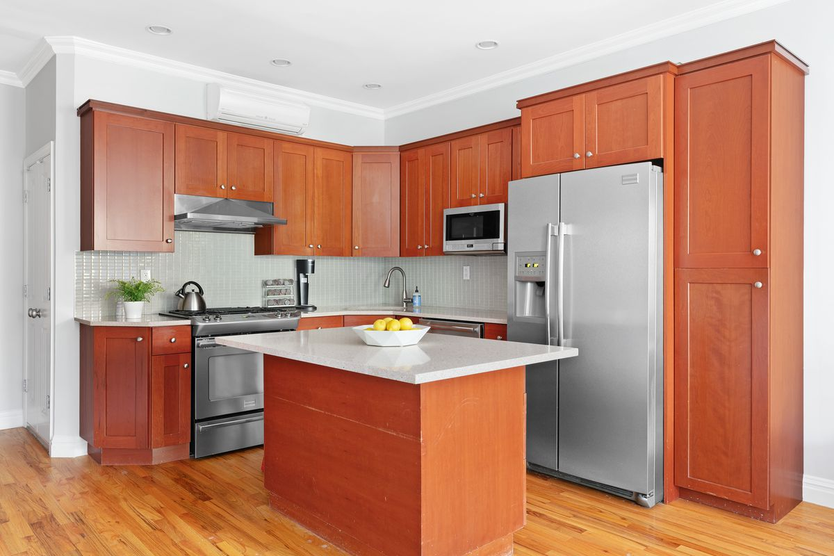 A kitchen with reddish brown cabinets and silver appliances. An island with white countertops sits at the center.