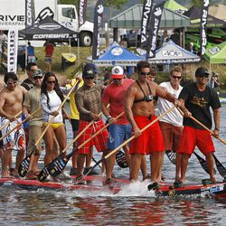 A giant stand up paddleboard rides past vendors during the Open Air Demo Day for the Outdoor Retailers Summer Market show  Wednesday, Aug. 3, 2011, around the Jordanelle Reservoir in Summit County, Utah.