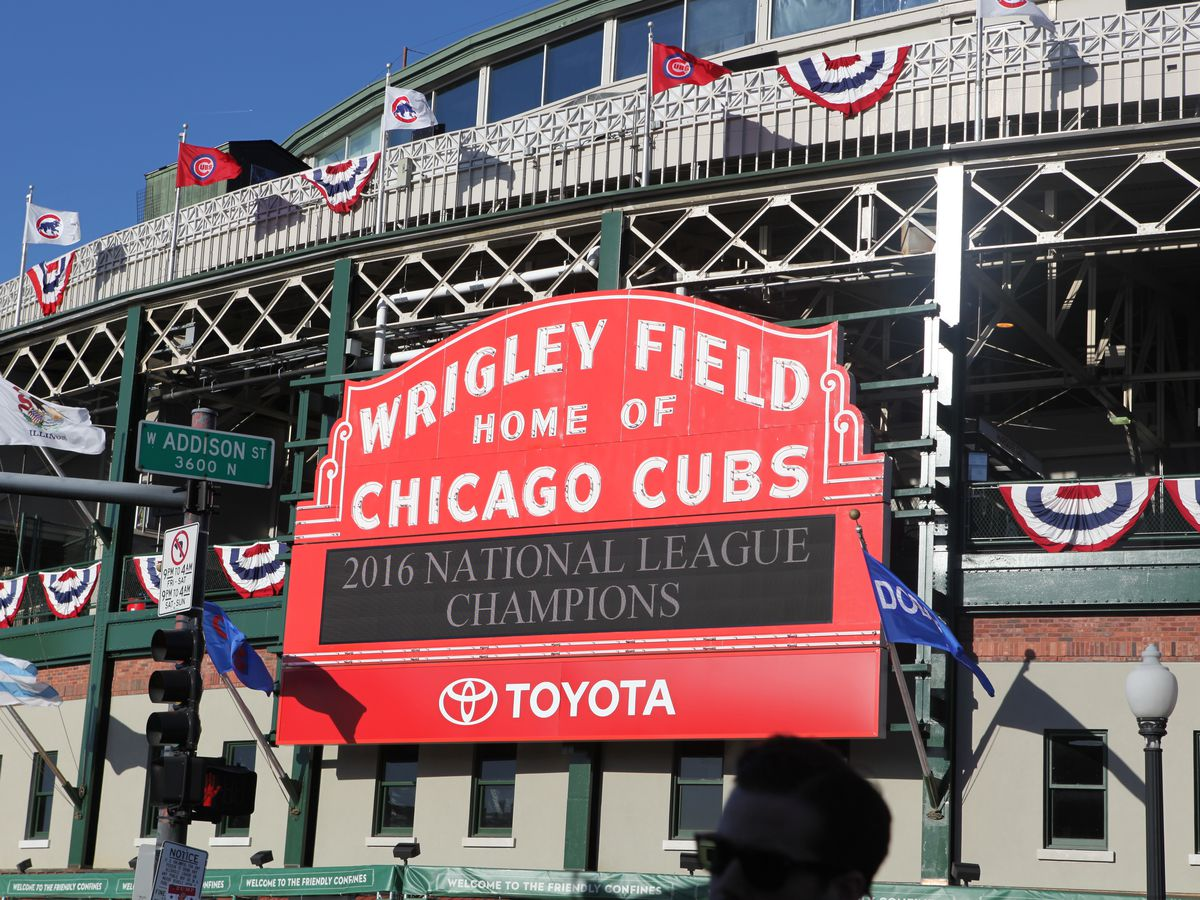 A red sign above the baseball field's entrance reads: Wrigley Field Home of the Chicago Cubs.