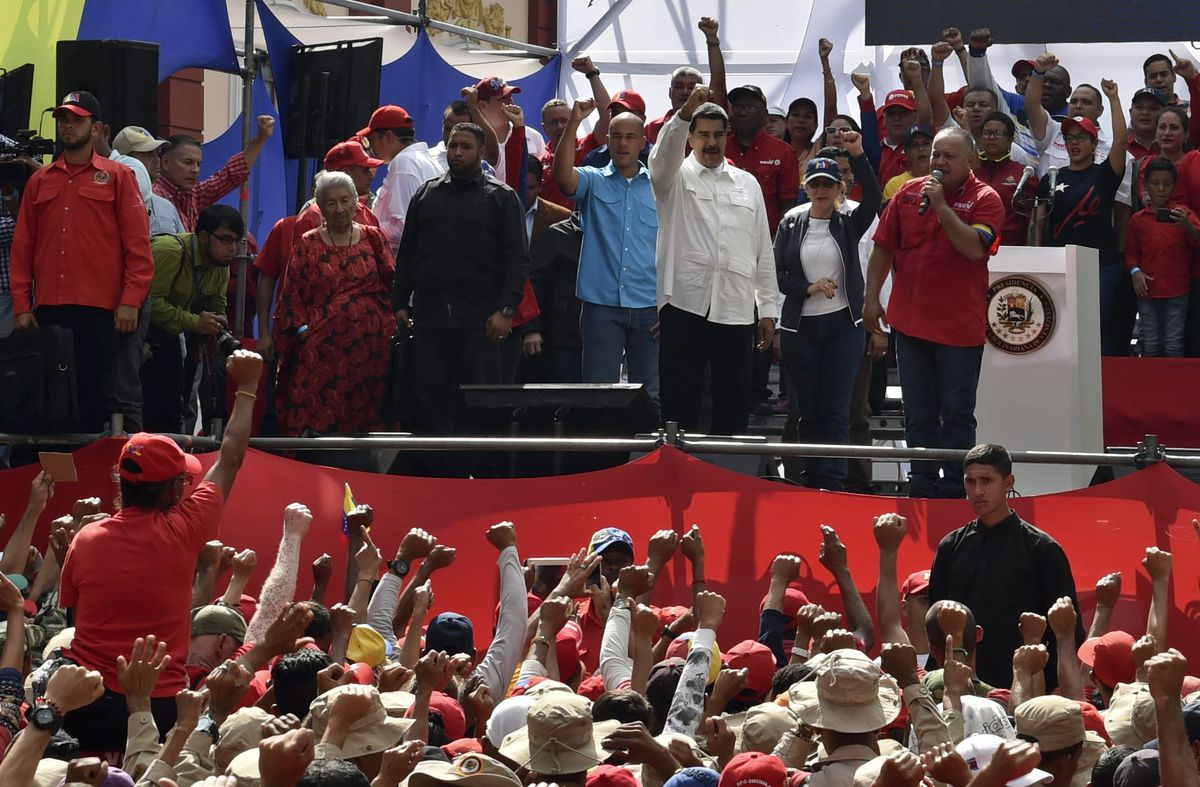 The head of Venezuela's Constituent Assembly Diosdado Cabello (R) speaks next to Venezuelan President Nicolas Maduro (C) during a rally at the Miraflores Presidential Palace on March 9, 2019.