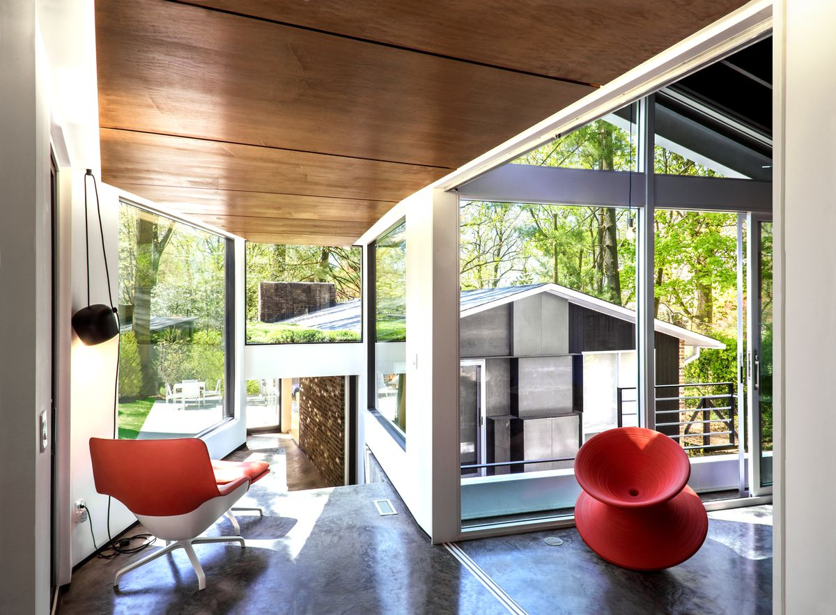 Living room with concrete floors and large glass windows overlooking another part of the house.