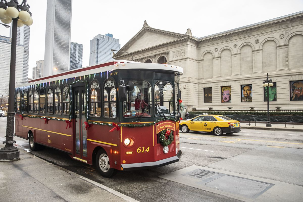 A trolley from the Chicago Trolley & Double Decker Co. pulls away after making a stop outside the Art Institute on Michigan Ave. Monday, Dec. 30, 2019.