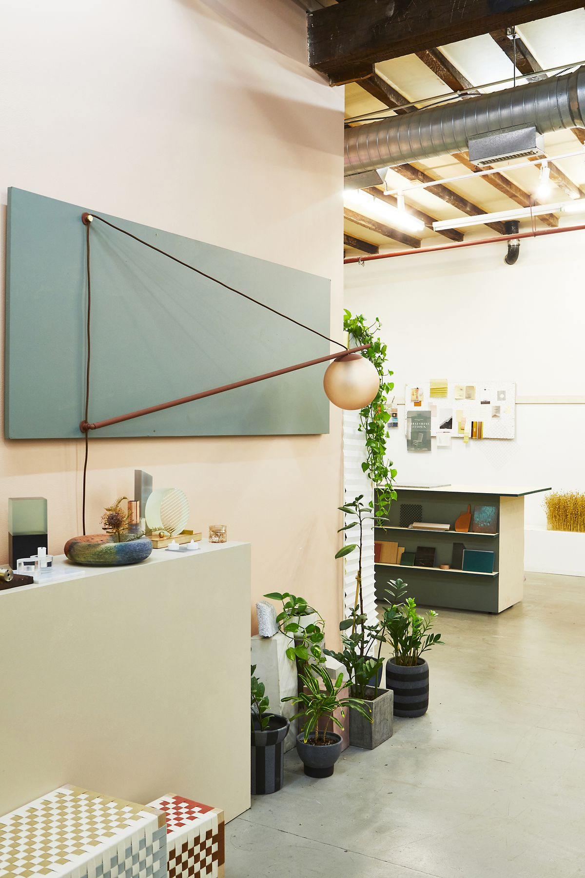 A corner of Ladies & Gentlemen Studio, has a light fixture attached to the wall that has a green background and brass and a round glass shade. There are a number of plants on the floor and a shelf with objects.