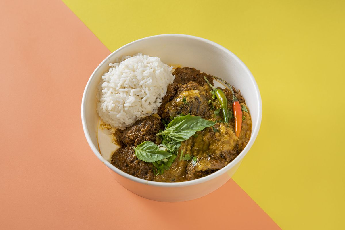 A bowl of curry and rice on a yellow and peach background