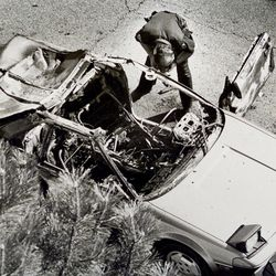 Police officer searches Mark Hofmann's car after a bomb exploded in it near 200 North and Main Street in Salt Lake City on Oct. 16, 1985.