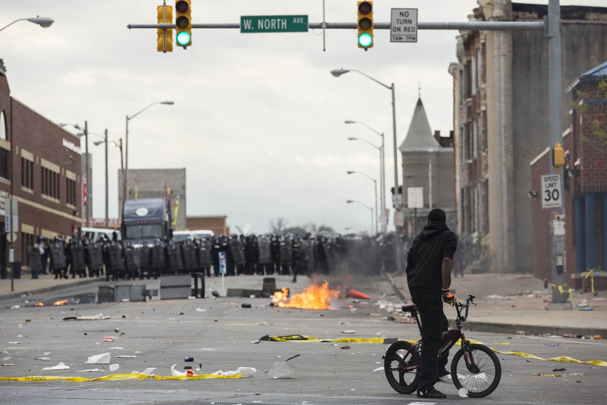 Police stand guard in Baltimore as riots and protests break out over the death of Freddie Gray while in police custody.