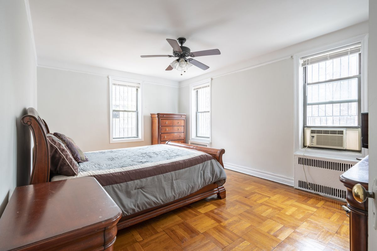 A bedroom with a small bed, wooden furniture, three windows, and hardwood floors.