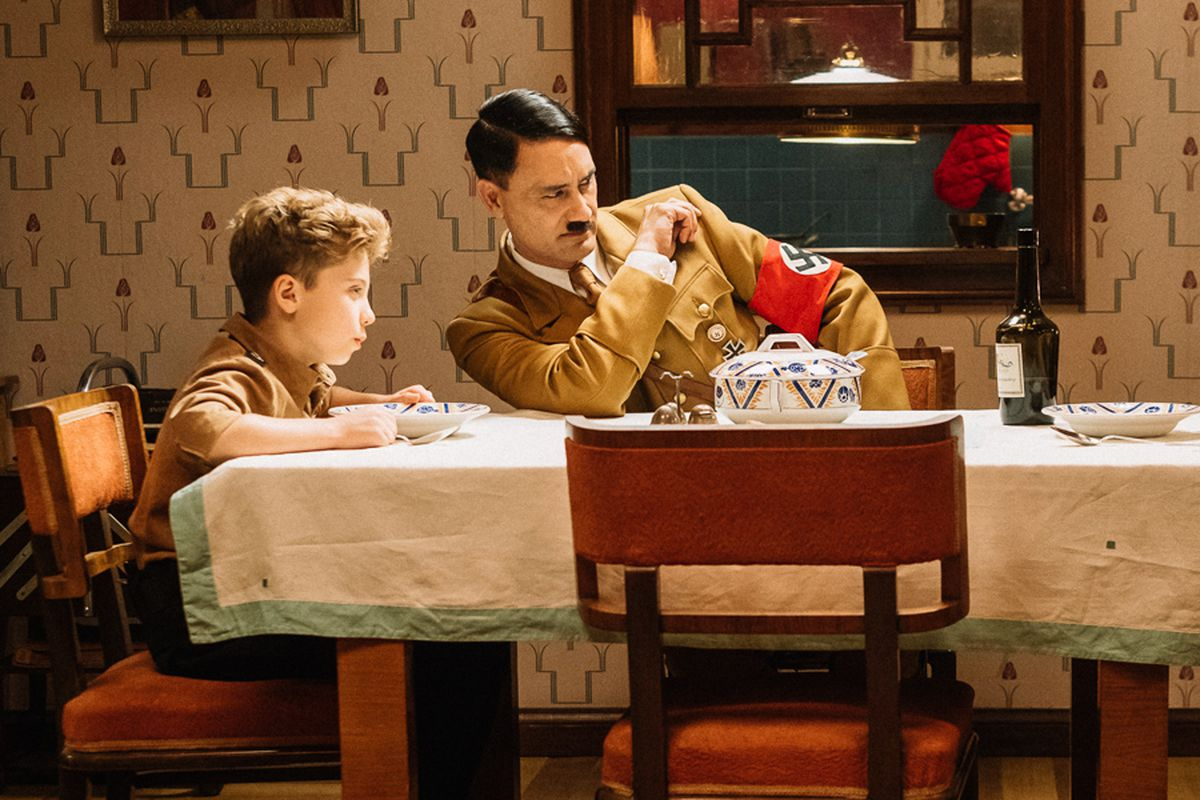 "Roman Griffin Davis, Taika Waititi at Hitler, and Scarlet Johansson sit around a dining table in the film ""Jojo Rabbit."""