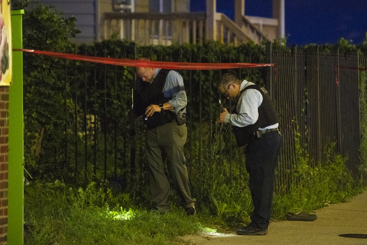 Police investigate the scene where a man was found with a gunshot wound to the head Sunday night in the 100 block of West 119th Street.   Tyler LaRiviere/Sun-Times