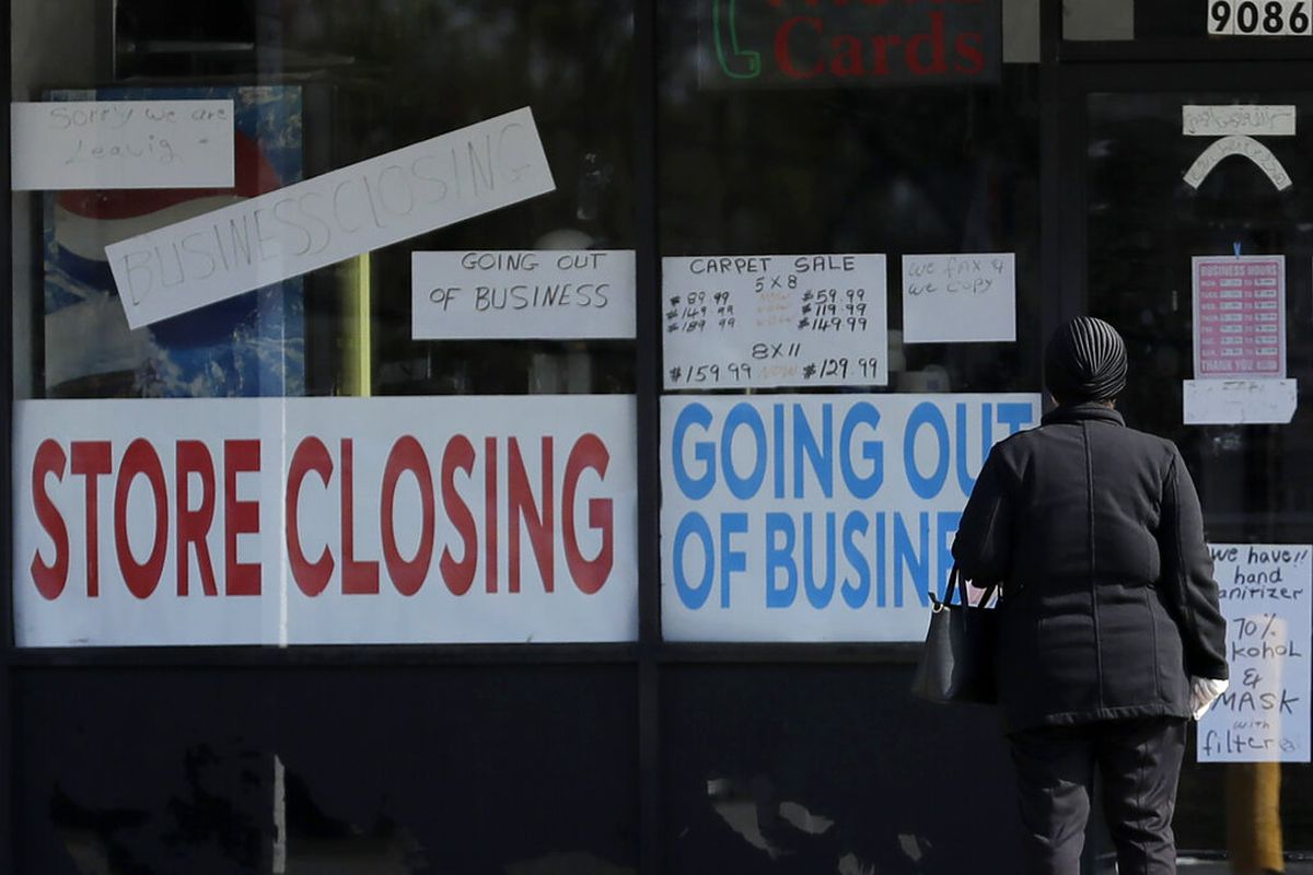 A woman looks at signs at a store closed due to COVID-19 in Niles, Illinois.