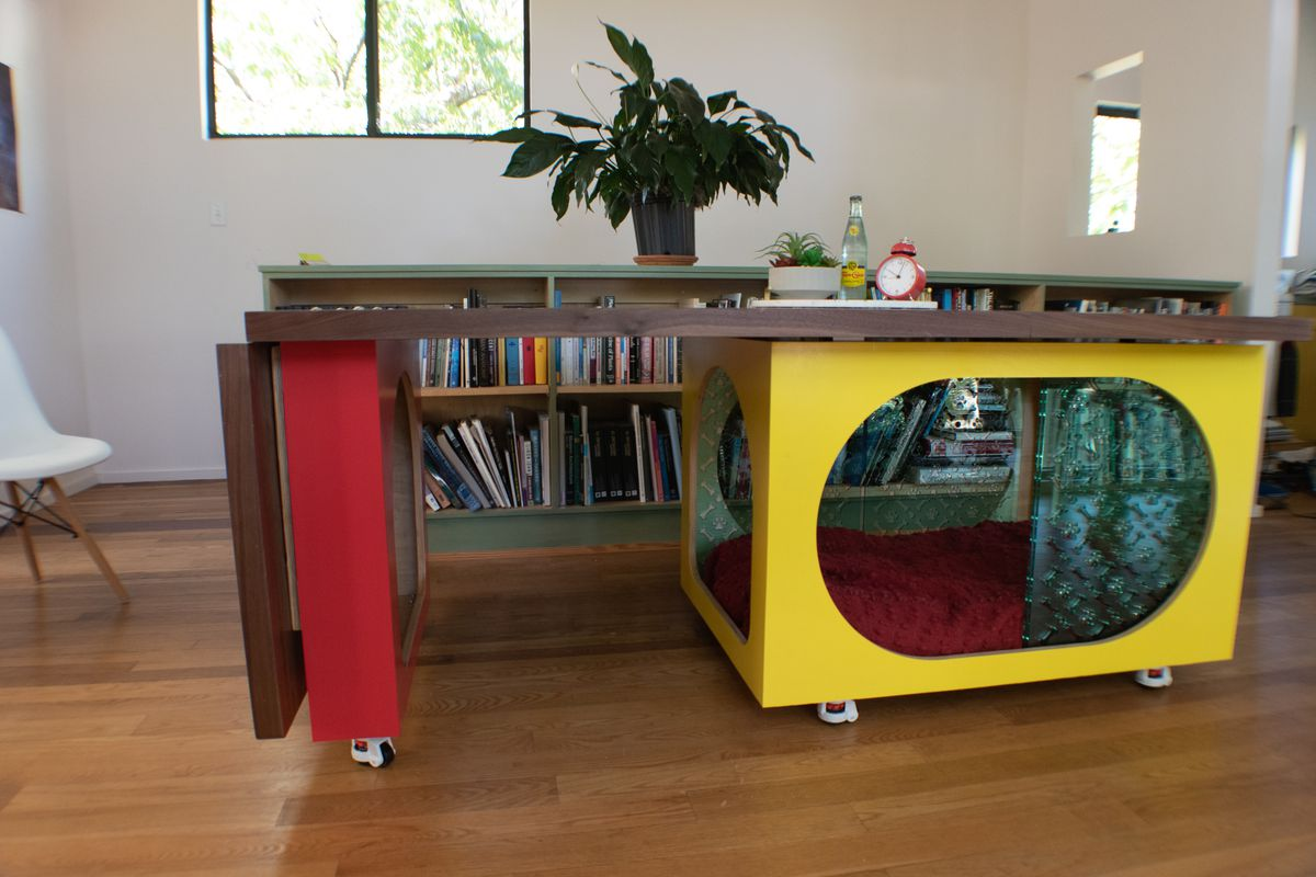 Interior photo of a table supported by a small rectangular box on wheels and a larger box on wheels on each end. The boxes have oval openings, and the larger one has dog bedding and curtain inside.