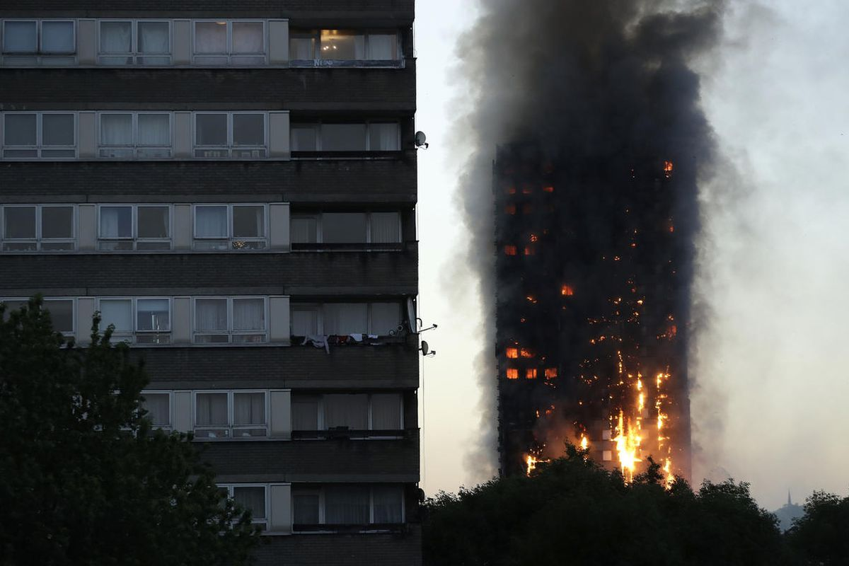 Smoke and flames rise from a building on fire in London, Wednesday, June 14, 2017. Metropolitan Police in London say they're continuing to evacuate people from a massive apartment fire in west London. The fire has been burning for more than three hours an