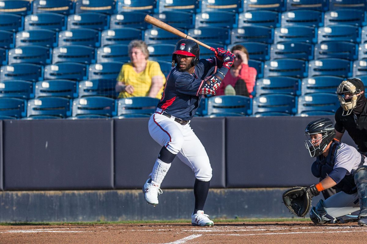 Michael Harris takes a swing for the Rome Braves during a day game. Camera is looking down the third base line at the left handed swinging Harris. Harris's foot is lifted in anticipation of the pitch and the catcher has his glove out to receive the ball.