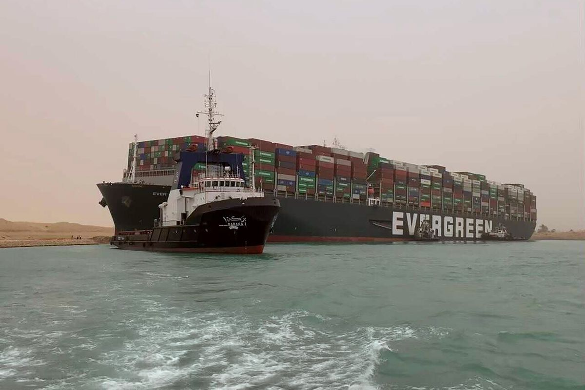 In this photo released by the Suez Canal Authority, a boat navigates in front of a massive cargo ship, named the Ever Green, rear, sits grounded Wednesday, March 24, 2021, after it turned sideways in Egypt's Suez Canal, blocking traffic in a crucial East-West waterway for global shipping. An Egyptian official warned Wednesday it could take at least two days to clear the ship.