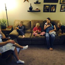 8-year-old Mykenzie Burton, center, reads aloud before bedtime as the rest of the family listens Sept. 25. From left is dad Kelly, 6-year-old Porter, mom Mary holding 2-month old Raiger and 3-year-old Logan.