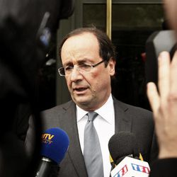 """French Socialist party candidate Francois Hollande, center, addresses journalists outside his apartment on the morning after the first round of the French presidential elections in Paris, France, Monday, April 23, 2012. Hollande has taken his plodding, undynamic campaign to become France's next president to within spitting distance of victory over the """"hyper-president"""" Nicolas Sarkozy, finishing first in Sunday's initial round of voting."""