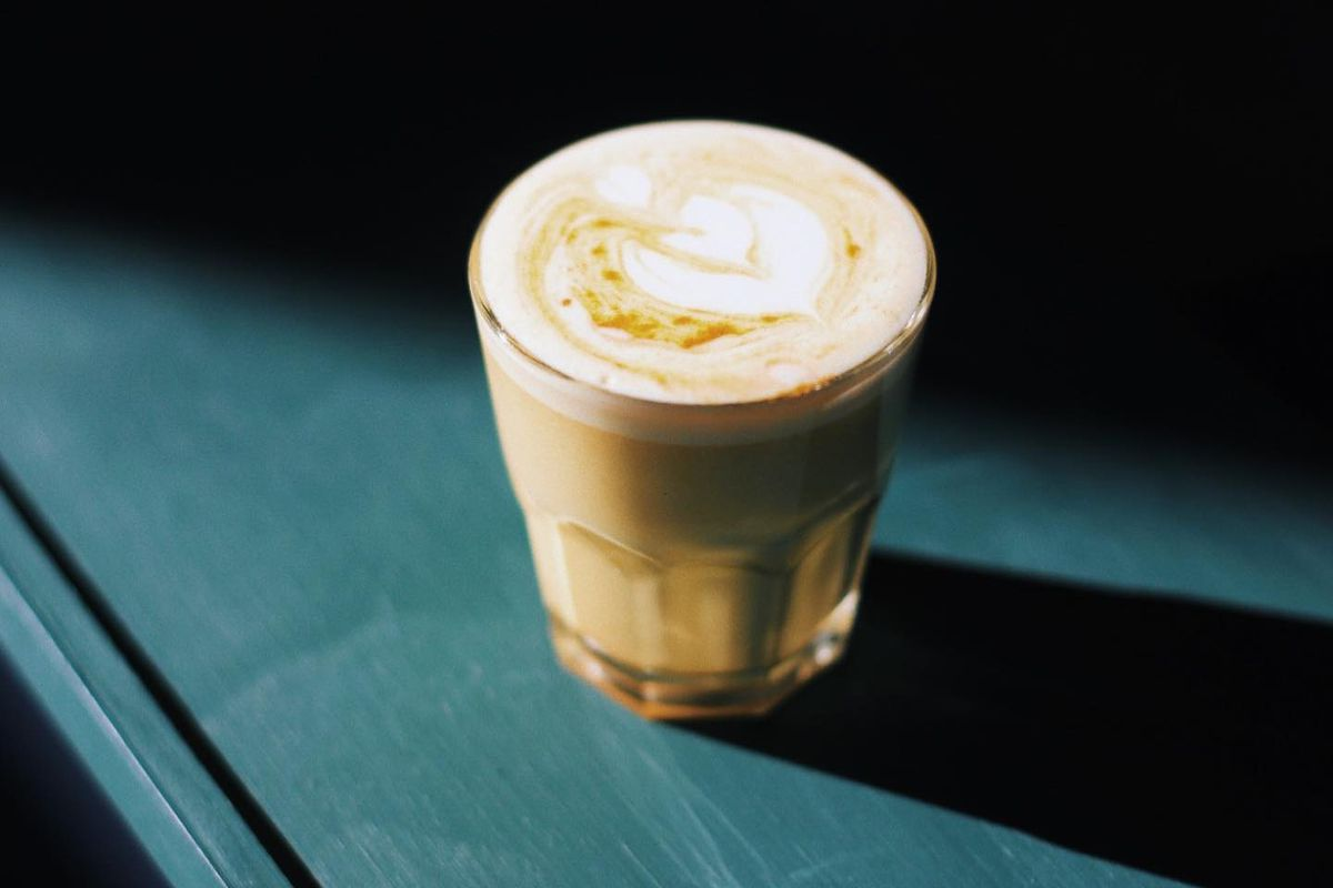 A golden latte with a heart-shaped flower etched at the top of the drink in a beveled glass sits atop a turquoise wood table with light shining on it from the font and a dark shadow in back