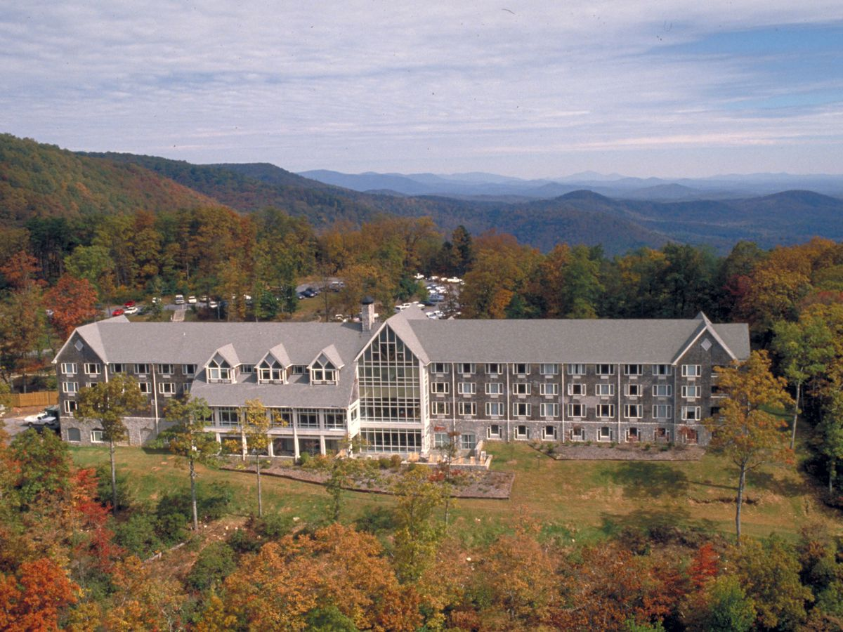 The exterior of a large lodge surrounded by multi-color trees in Autumn.