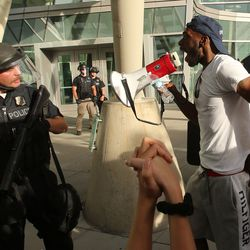 A demonstrator uses a bullhorn to yell at an officer during a protest at the Public Safety Building in Salt Lake City on Monday, June 1, 2020.
