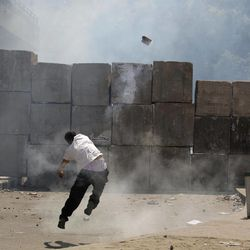 An Egyptian protester throws back a tear gas canister toward riot police, unseen, behind cement blocks that are used to close the street leading to the U.S. embassy during clashes in Cairo, Egypt, Friday, Sept. 14, 2012, as part of widespread anger across the Muslim world about a film ridiculing Islam's Prophet Muhammad.
