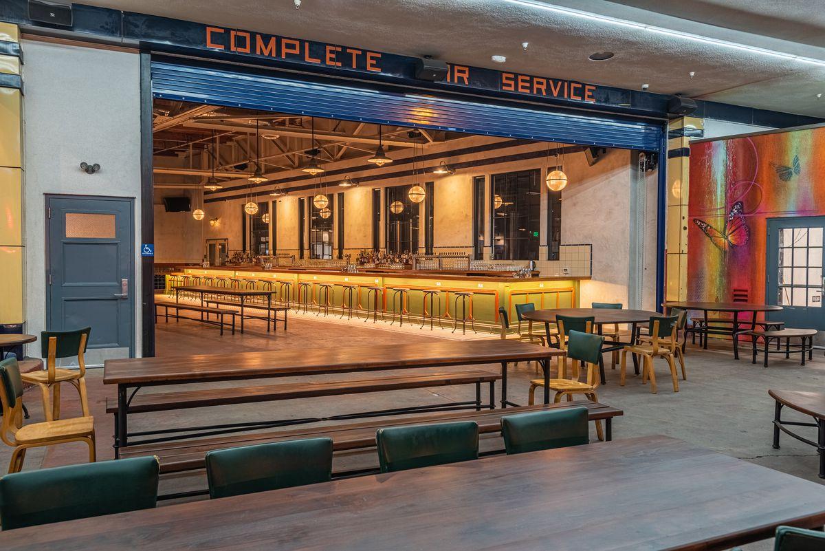 A retrofitted interior of a beer bar inside a former auto body shop.