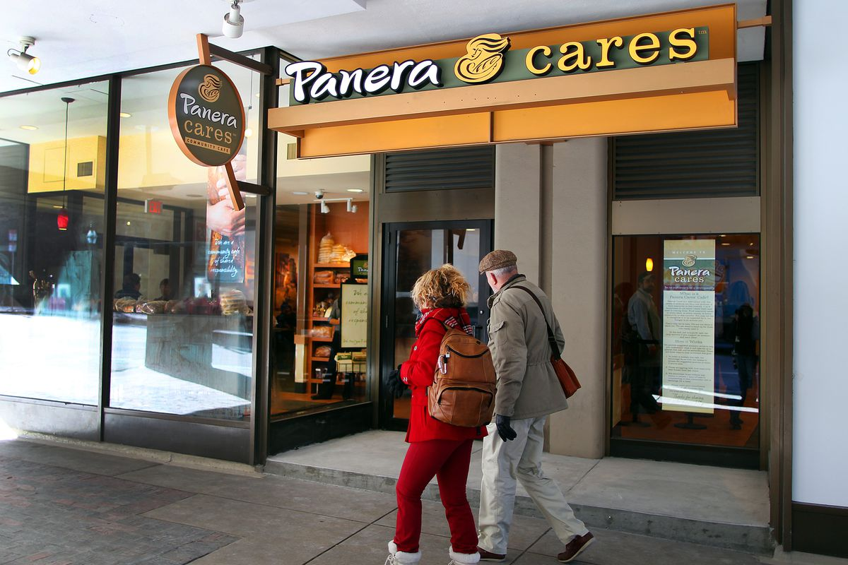 A couple walks past the storefront of Panera Care.