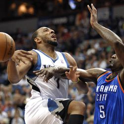 Oklahoma City Thunder's Kendrick Perkins, right, bats the ball away from Minnesota Timberwolves' Derrick Williams as Williams attempts to go to the basket during the first quarter of an NBA basketball game, Saturday, April 14, 2012, in Minneapolis. (AP Photo/Tom Olmscheid)