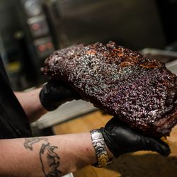 Andy Husbands prepares to slice up a half rack of ribs at The Smoke Shop.
