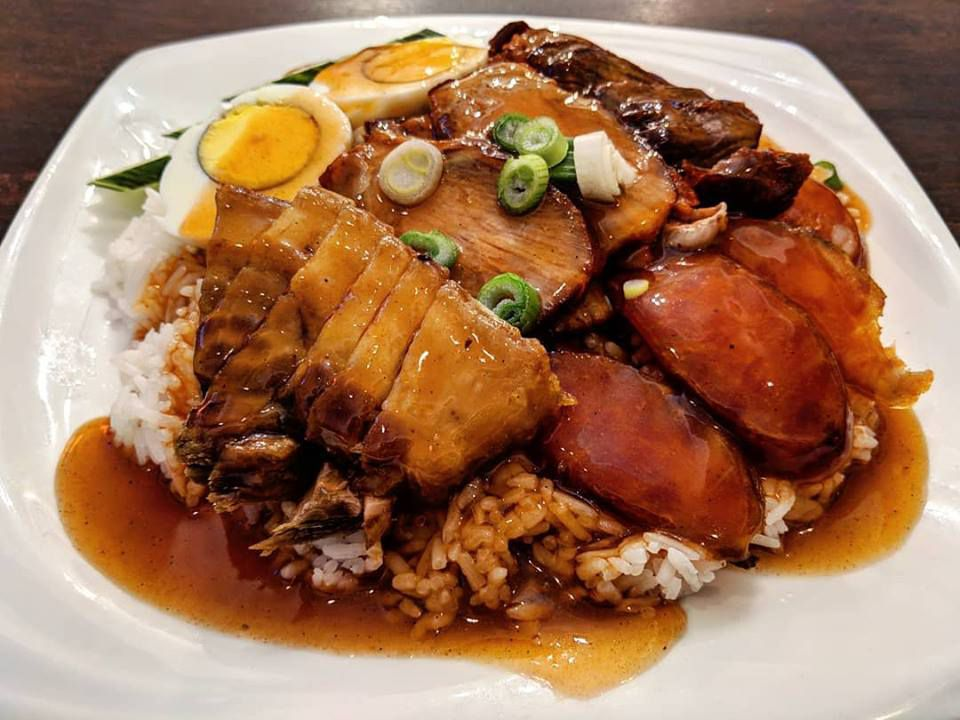 Pork belly, grilled pork, and Chinese sausage sit atop a plate of white rice with a hard boiled egg. A brown sauce is drizzled over the whole thing.